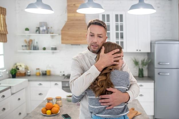 Troskliwy i kochający ojciec mocno przytulający córkę, wypowiadający jej miłe słowa.