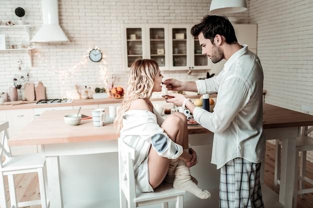 Troskliwy mąż. brunetka, brodaty mężczyzna w białej koszuli, czuje się dobrze podczas karmienia żony w kuchni