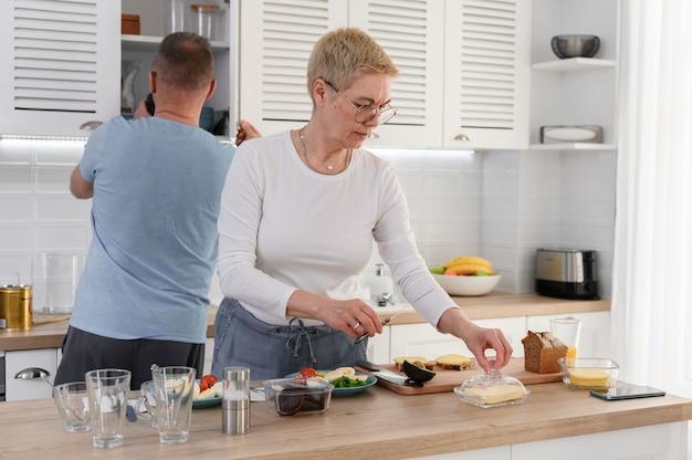 Troskliwy mąż w podeszłym wieku pomaga kochającej starszej żonie przy kolacji romantyczna para starszych gotuje śniadanie o godz