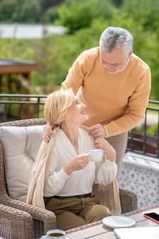 Troskliwy mąż w średnim wieku zakrywający pledem zadowolonej, atrakcyjnej żony małżonki