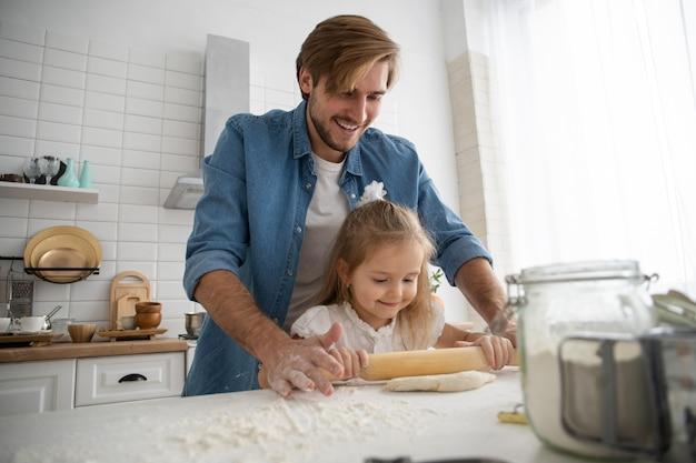 Troskliwy młody kaukaski ojciec i urocza mała córka przedszkolaka piec razem w kuchni w domu, szczęśliwy kochający tata uczy małe dziewczynki gotowanie, przygotowywanie naleśników lub ciastek na śniadanie