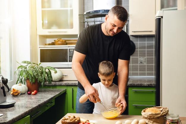 Troskliwy ojciec uczy syna gotować. aktywność wewnętrzna. świetnie spędzony czas z rodziną