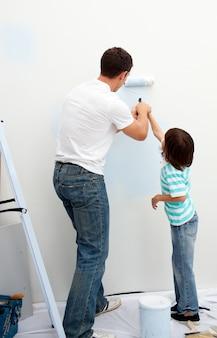 Troskliwy ojciec uczy syna, jak malować