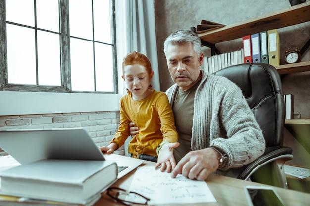 Troskliwy tata. poważny miły człowiek siedzi z córką, wskazując na kartkę papieru