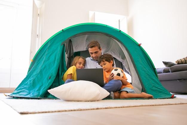 Troskliwy tata siedzi ze skrzyżowanymi nogami z dziećmi w namiocie w domu i patrzy na ekran laptopa. urocze dzieci oglądają film na komputerze z ojcem. koncepcja dzieciństwa, czasu rodzinnego i weekendu