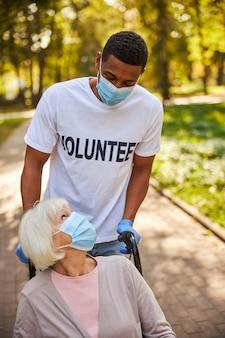 Troskliwy wolontariusz w białej koszulce i niebieskich rękawiczkach asystuje emerytowanej kobiecie i toczy jej wózek inwalidzki po drodze