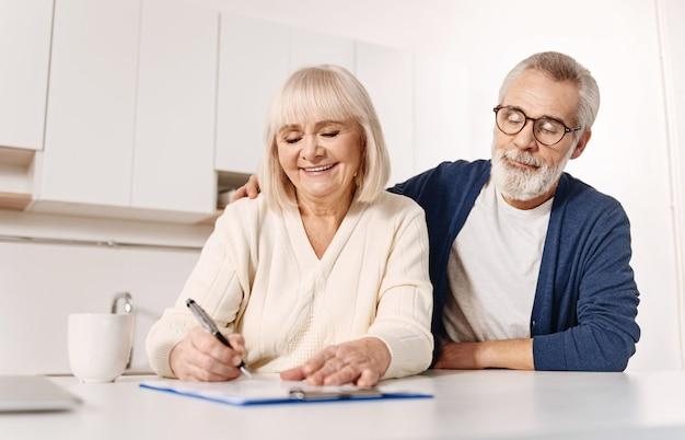 Troszczymy się o przyszłość naszych wnuków. uśmiechający się harmoniczny pozytywny starsza kobieta siedzi w domu obok męża i wyraża radość podczas podpisywania dokumentów