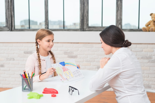 Troszkę blondynki dziewczyny seansu rysujący dom na papierze jej żeński psycholog