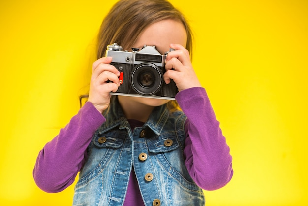 Troszkę śliczna dziewczyna robi fotografii na kolorze żółtym