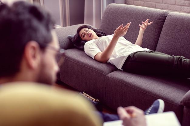 Trudna sytuacja. ładna, dobrze wyglądająca kobieta, która patrzy na terapeutę i dzieli się z nim swoimi obawami