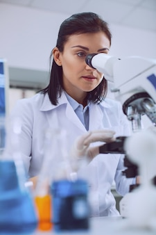 Trudne badania. skoncentrowana inteligentna naukowiec pracująca z mikroskopem i ubrana w mundur