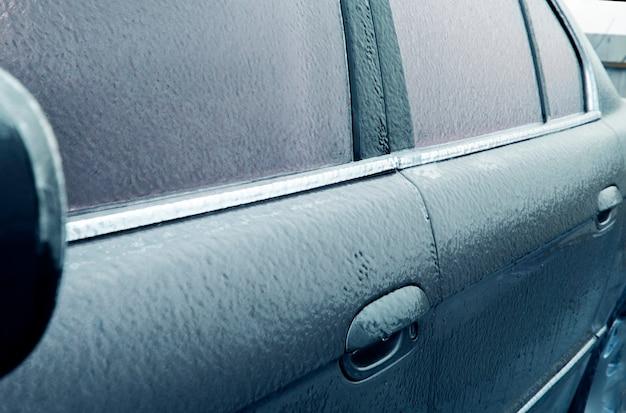 Trudne warunki meteorologiczne zimą, koncepcja złej pogody, lód na drogach, ostrzeżenie przed burzą i pomarańczowy poziom zagrożenia. zamarznięty samochód selektywnej ostrości i niebieskiego tonowania.