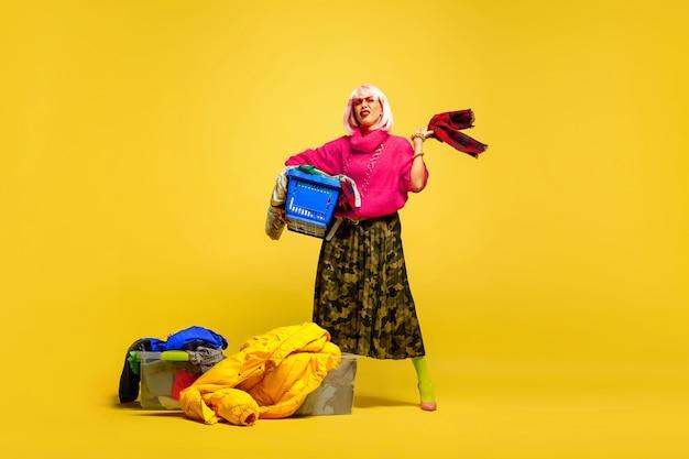 Trudno być influencerem. dłuższe pranie z kolekcją ubrań. portret kobiety kaukaski na żółtym tle. piękny model blondynka. pojęcie ludzkich emocji, wyraz twarzy, sprzedaż, reklama.
