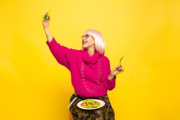 Trudno być influencerem. najpierw selfie, później jedzenie. trzeba wcześniej zastrzelić danie. portret kobiety kaukaski na żółto. piękny model blondynka. pojęcie ludzkich emocji, wyraz twarzy, sprzedaż, reklama.