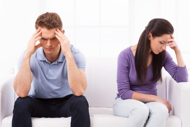 Trudności w związku. przygnębiony młody mężczyzna i kobieta siedzą blisko siebie na kanapie i trzymają głowę w dłoniach