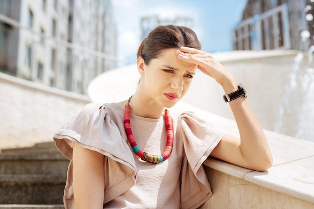 Trudny okres. przygnębiona nieszczęśliwa kobieta dotyka czoła, myśląc o swoich problemach