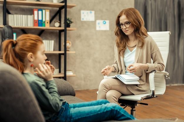 Trudny przypadek. miła profesjonalna psycholog komunikuje się ze swoim pacjentem podczas wykonywania swojej pracy