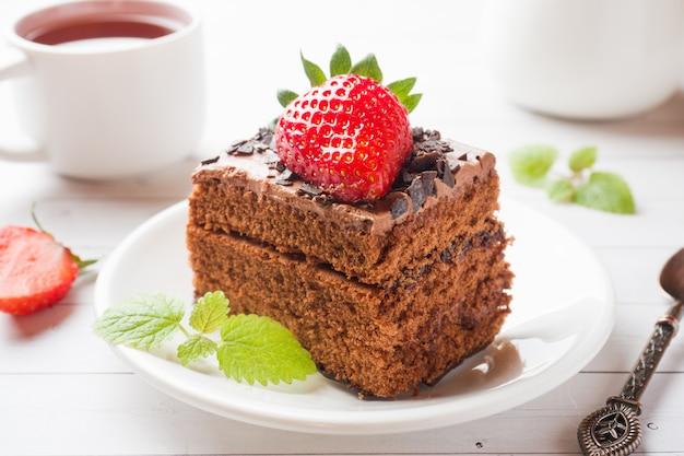 Trufla tort z czekoladą i truskawkami i mennicą na białym drewnianym stole. selektywne skupienie.