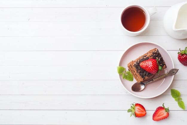 Trufla tort z czekoladą i truskawkami i mennicą na białym drewnianym stole.