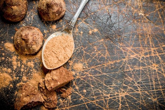Trufle czekoladowe z kakao w proszku. na drewnianym tle.