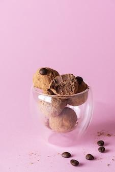 Trufle kawowe w szklance na różowym tle
