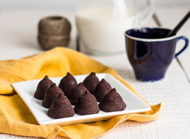 Trufle z ciemnej czekolady gotowe do spożycia na białym drewnianym