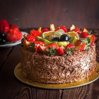 Truskawka, czekoladowy tort owocowy i świeża truskawka na drewnianym stole