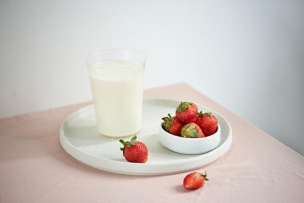 Truskawka i jogurt na różowym tle