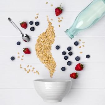 Truskawka, jagoda, orzeszki piniowe i płatki owsiane leje się w ceramicznej misce do gotowania domowego musli lub muesli