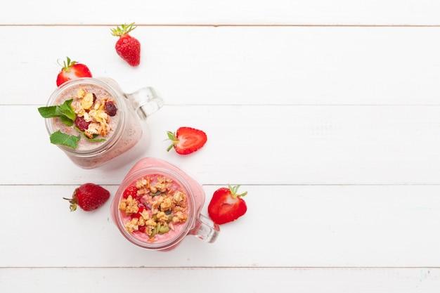 Truskawka z jogurtem na biały rustykalny drewniany. deser kremowy