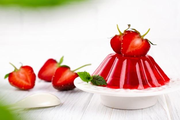 Truskawki galareta na bielu talerzu. letni deser z galaretką owocową i świeżą truskawką.