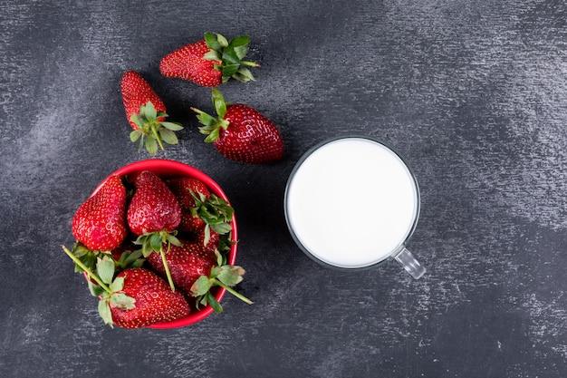 Truskawki leżą płasko w misce, a inne przy filiżance mleka na ciemnym stole