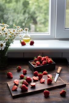 Truskawki na drewnianym stole w kuchni z bukietem stokrotek i tekstyliów, domowe zdrowe jedzenie, koncepcja lato, z bliska.