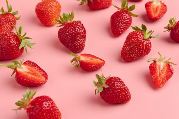 Truskawki na różowym tle. koncepcja świeżej żywności ekologicznej
