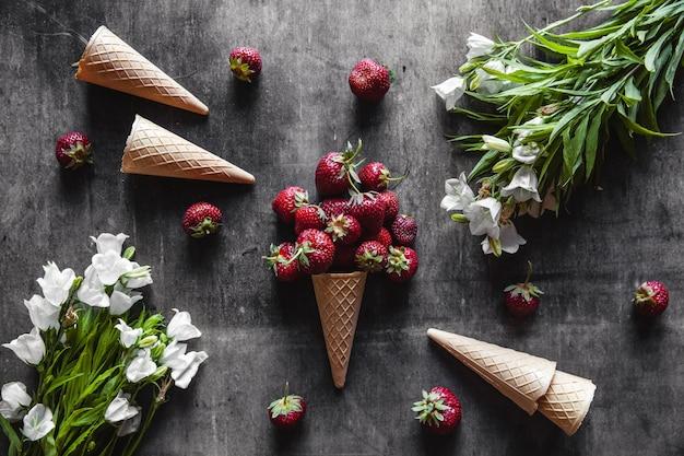 Truskawki w filiżankach na ciemnoszarej powierzchni z goframi i białymi kwiatami. zdrowa żywność, owoce