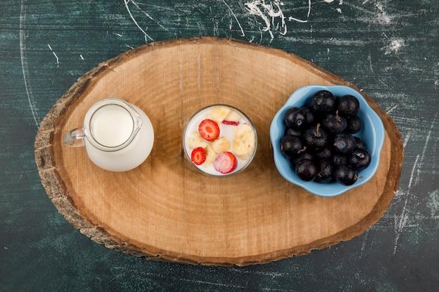 Truskawki w śmietanie podawane z mlekiem i wiśniami na drewnianym talerzu, widok z góry