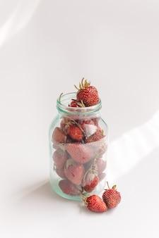 Truskawki w szklanym słoju. letnia kompozycja, minimalistyczny styl