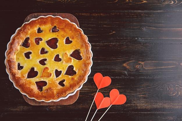 Truskawkowe ciastko na walentynki z serca na drewnianym stole