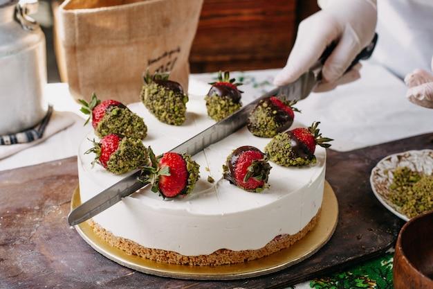 Truskawkowe ciasto kremowe pokrojone przez kucharza pyszne pyszne ciasto słodkie w kuchni
