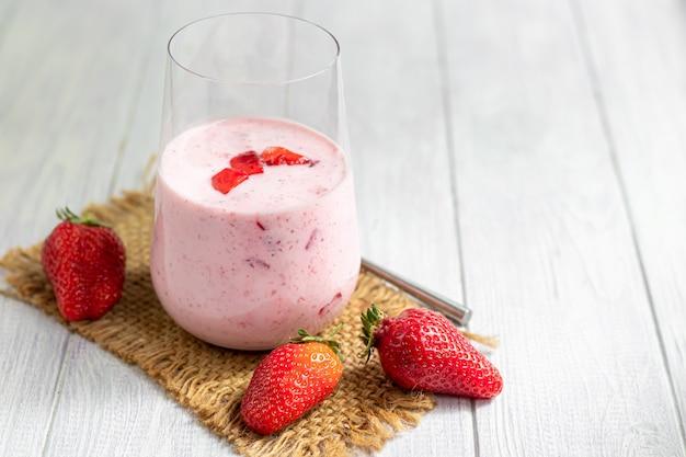 Truskawkowe i jogurtowe koktajle na białym stole. ozdobiony kwiatami bzu czarnego i truskawkami. zdrowe odżywianie, dieta.