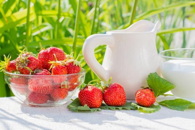Truskawkowe jagody i liście, dzbanek i filiżanka z mlekiem na pielusze na tle trawy