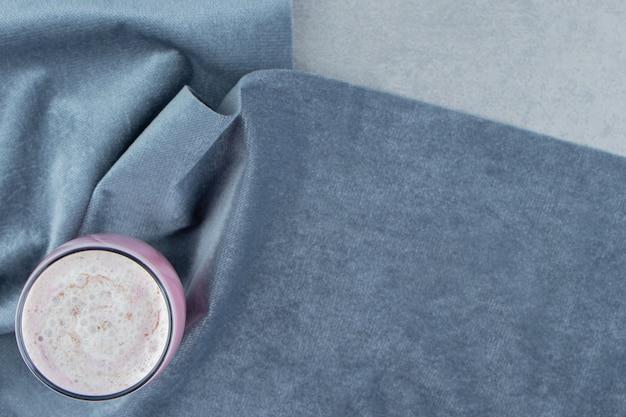 Truskawkowe mleko wstrząsnąć ręcznikiem na marmurowym tle. wysokiej jakości zdjęcie