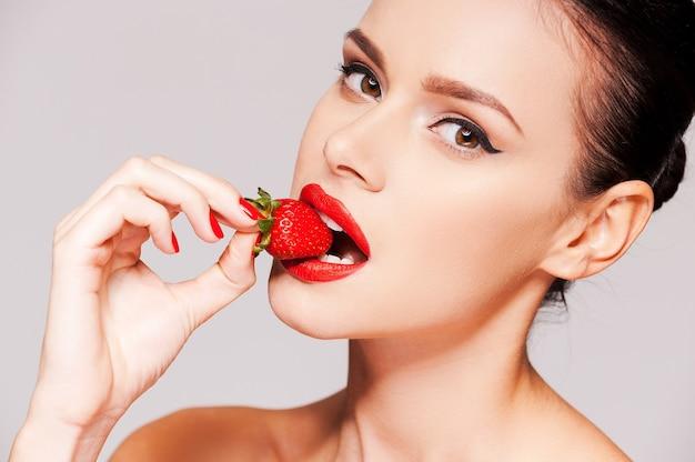 Truskawkowe usta. piękna młoda kobieta bez koszuli trzymająca truskawkę w dłoni i degustująca ją, stojąc na szarym tle