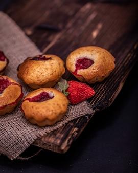 Truskawkowy słodka bułeczka i kawowe fasole na drewnianej desce na ciemnym drewno stole