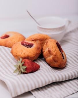 Truskawkowy słodka bułeczka z świeżymi truskawkami na stole.