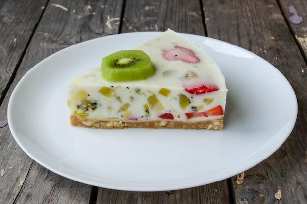 Truskawkowy tort jogurtowy ozdobiony owocami tropikalnymi kiwi i truskawka ustawiony na białym talerzu gotowy do kawy