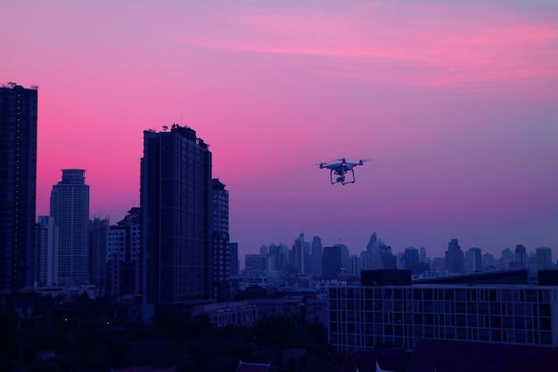 Trutnia latanie w wieczór niebie nad drapaczami chmur bangkok podmiejski, tajlandia