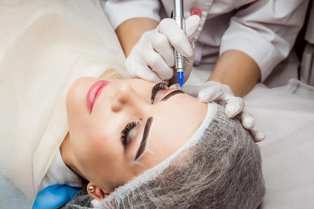 Trwały makijaż brwi. zbliżenie piękna kobieta z grubymi brwiami w salonie piękności. kosmetyczka robi tatuaż do brwi dla kobiecej twarzy. procedura kosmetyczna.