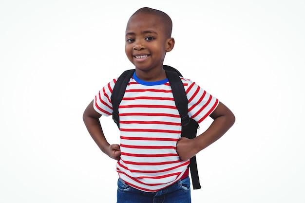 Trwanie chłopiec z plecakiem ono uśmiecha się przy kamerą