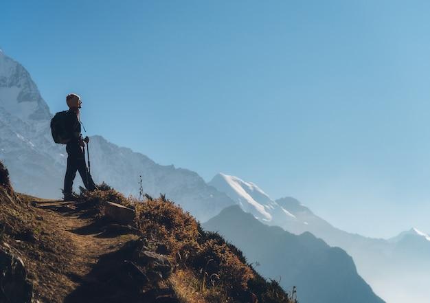 Trwanie młoda kobieta z plecakiem na wzgórzu i patrzeć na górach